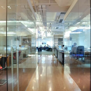 Glass partitions separating various individual rooms in busy large office