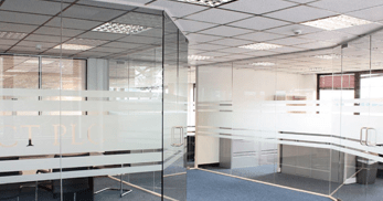 Glass partitioning within office with frosted sections for privacy