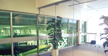 Glass partitioning separating various rooms and overlooking glass walls in to a replica airplane hanger within an RAF museum
